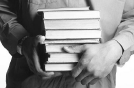man holding stack of books 1.png